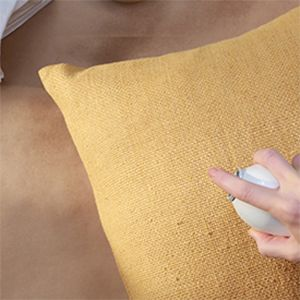 person spraying yellow pillow with Scotchgard Fabric Protector